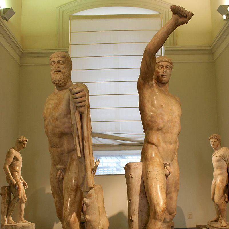 """Dwaj zakochani w sobie mężczyźni, którzy z żądzy zemsty za upokorzenie i zazdrości postanowili obalić ateńskiego tyrana. Na ilustracji fragment tzw. """"Grupy Tyranobójców"""" (przedstawiająca słynną parę) uważanej za pierwszy pomnik historyczny w Atenach i symbol demokracji."""