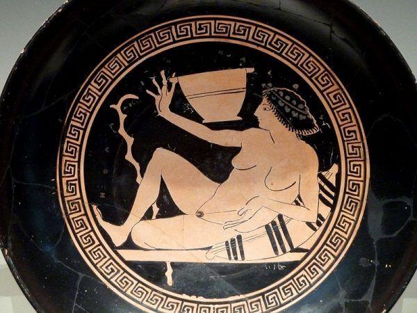 """Malowidła wazowe stanowią dobre źródło informacji o prostytucji w starożytnej Grecji. Obraz wewnątrz kyliksu przedstawia heterę grającą w znaną z sympozjonów """"grę pitną""""."""