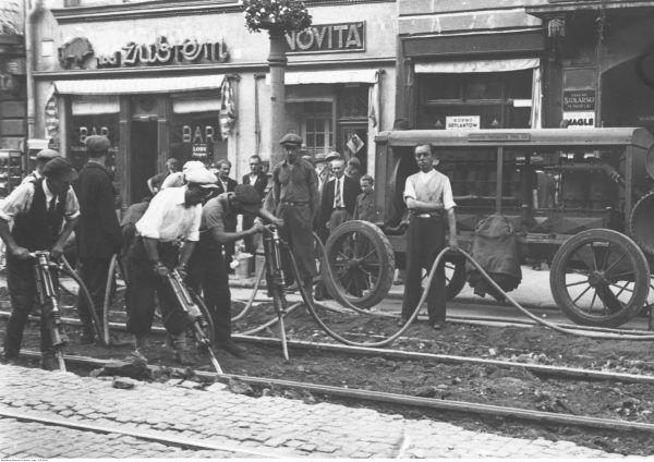 """Wymiana torów tramwajowych w przedwojennej Warszawie. W tle widać bar """"Pod Żubrem"""". Zdaniem ówczesnych specjalistów, przynajmniej tych spoza Polski, właśnie bary mogły stanowić miejsca szczególnie niebezpieczne dla kobiet."""