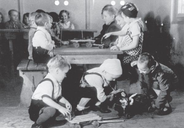 """Propagandowe zdjęcie pokazujące, jak dobrze miało się żyć dzieciom robotnic przymusowych w specjalnych ośrodkach. Ilustracja i podpis z książki """"Teraz jesteście Niemcami. Wstrząsające losy zrabowanych polskich dzieci""""."""