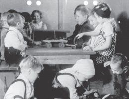 """Propagandowe zdjęcie pokazujące, jak dobrze miało się żyć dzieciom robotnic przymusowych w specjalnych ośrodkach. Ilustracja i podpis z książki """"Teraz jesteście Niemcami""""."""