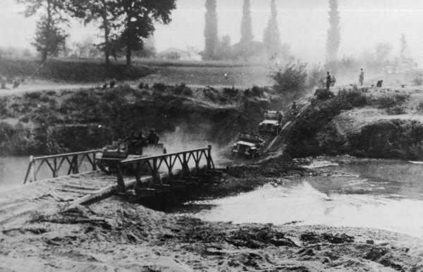 """Żołnierze z 2 Korpusu Polskiego przekraczają rzeką Idice na moście Baileya. Zdjęcie i podpis z książki """"Polskie triumfy""""."""