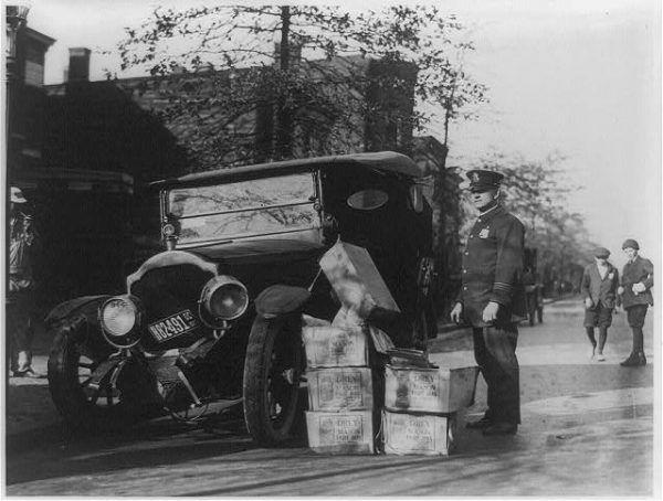 Policjant pilnujący skonfiskowany samogon, przez Amerykanów określany jako moonshine lub mountain dew