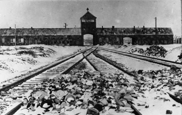 Tory kolejowe, wartownia i brama główna Auschwitz II (Birkenau), widok z rampy wewnątrz obozu, 1945