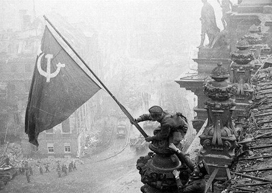 Czerwonoarmiści wywieszający flagę ZSRR na dachu Reichstagu. Zdjęcie wykonał Jewgienij Chałdiej.