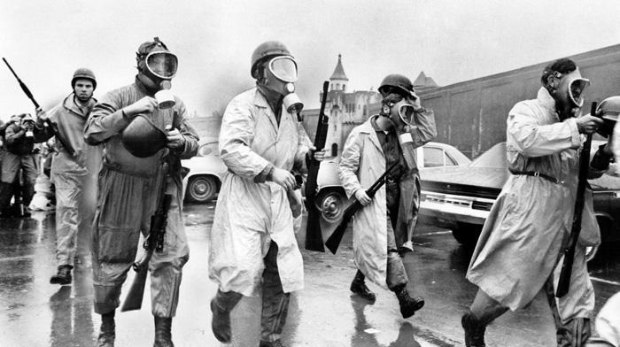 Funkcjonariusze nowojorskiej policji w maskach gazowych i płaszczach przeciwdeszczowych w drodze do wejścia do więzienia. (Dzięki uprzejmości Dona Duttona/Getty Images)