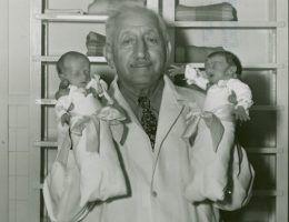 """Martin A. Couney, znany jako Doktor Inkubator, pozuje z dwójką """"swoich"""" wcześniaków."""