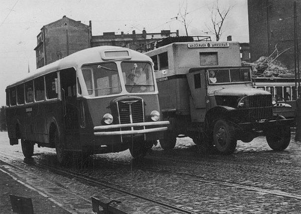 Autobus Chausson na warszawskiej ulicy, obok widoczny samochód ciężarowy przewożący pasażerów